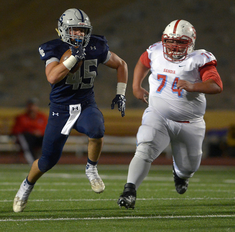 gbs102016i/SPORTS -- La Cueva's Josh Woisin, 45, dashes by Sandia's Adam Lucero, 72, during the game at Wilson Stadium on Thursday, October 20, 2016.(Greg Sorber/Albuquerque Journal)