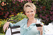 Smiling Woman Enjoying a Glass of Red Wine