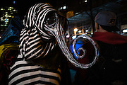 New York, NY - 31 October 2016. A man is a striped costume including a mask with a long, curling proboscis,  in the Greenwich Village Halloween Parade.
