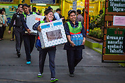 "01 FEBRUARY 2014 - BANGKOK, THAILAND: Election workers carry ballot boxes to a waiting car in central Bangkok. Thais went to the polls in a ""snap election"" Sunday called in December after Prime Minister Yingluck Shinawatra dissolved the parliament in the face of large anti-government protests in Bangkok. The anti-government opposition, led by the People's Democratic Reform Committee (PDRC), called for a boycott of the election and threatened to disrupt voting. Many polling places in Bangkok were closed by protestors who blocked access to the polls or distribution of ballots. The result of the election are likely to be contested in the Thai Constitutional Court and may be invalidated because there won't be quorum in the Thai parliament.    PHOTO BY JACK KURTZ"