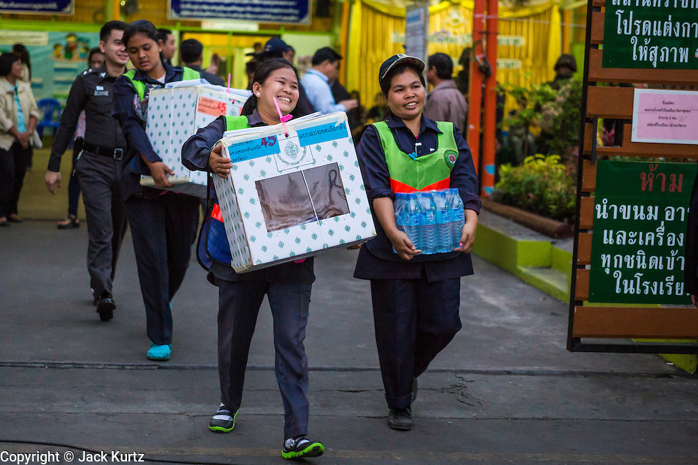 """01 FEBRUARY 2014 - BANGKOK, THAILAND: Election workers carry ballot boxes to a waiting car in central Bangkok. Thais went to the polls in a """"snap election"""" Sunday called in December after Prime Minister Yingluck Shinawatra dissolved the parliament in the face of large anti-government protests in Bangkok. The anti-government opposition, led by the People's Democratic Reform Committee (PDRC), called for a boycott of the election and threatened to disrupt voting. Many polling places in Bangkok were closed by protestors who blocked access to the polls or distribution of ballots. The result of the election are likely to be contested in the Thai Constitutional Court and may be invalidated because there won't be quorum in the Thai parliament.    PHOTO BY JACK KURTZ"""