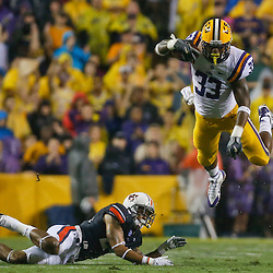 Sep 21, 2013; Baton Rouge, LA, USA; LSU Tigers running back Jeremy Hill (33) leaps over Auburn Tigers defensive back Ryan Smith (24) on a run during the first quarter of a game at Tiger Stadium. Mandatory Credit: Derick E. Hingle-USA TODAY Sports