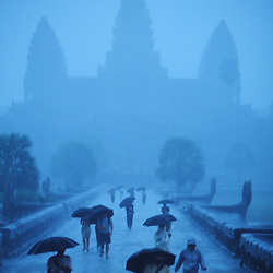 The massive carved towers of Angkor Wat silhouetted by monsoonal rains. Cambodia