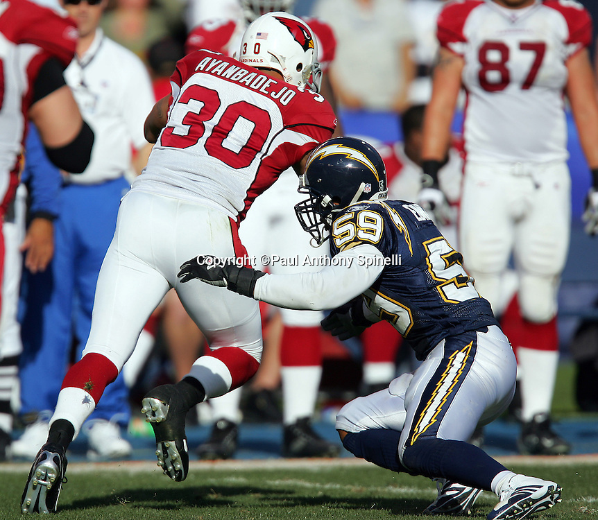SAN DIEGO - DECEMBER 31:  Fullback Obafemi Ayanbadejo #30 of the Arizona Cardinals tries to elude a tackle by linebacker Donnie Edwards #59 of the San Diego Chargers at Qualcomm Stadium on December 31, 2006 in San Diego, California. The Chargers defeated the Cardinals 27-20 to secure the number one seed in the AFC playoffs. ©Paul Anthony Spinelli *** Local Caption *** Obafemi Ayanbadejo;Donnie Edwards