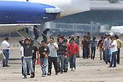 Guatemalan deportees exit a plane and head for the Migration Office in Guatemala City's La Aurora Airport after having been deported from the United States. Each week, fourteen flights arrive at La Aurora Airport from the U.S. carrying 135 deportees per airplane. Mostly men, the would-be migrants spend an average of two months at U.S. detention centers before they are sent back. From January 1st to May 17th, 2013, there have been 18,073 people deported back to Guatemala. Guatemala City, Guatemala. May 17, 2013.