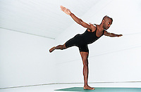 African American man holdinga yoga pose while balanced on one foot.