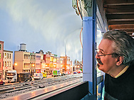 Farmingdale, New York, USA. January 21, 2018. Visitor BOB YORBURG, from Yorktown, inspects model train trolley town during TMB Model Train Club Open House at the Train Masters of Babylon 4,000 sqare feet Headquarters.
