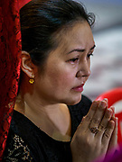 04 SEPTEMBER 2017 - BANGKOK, THAILAND: A woman prays after donating a sack of rice to Chaomae Thapthim Shrine. About 1,000 people came to Chaomae Thapthim Shrine for the annual food distribution. Staples, like rice and cooking oil, are donated to the shrine throughout the year and donated to poor people from the communities around the shrine. Food distributions like this are a tradition at Chinese shrines in Bangkok and a common way of making merit for the people who donate the staples.     PHOTO BY JACK KURTZ