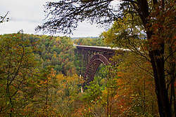 The New River Gorge Bridge - shot on a very overcast and cloudy day, the rusty patina on the bridge and the brilliance of the fall colors of the trees and foliage shine.  The bridge is one of the longest single arch steel span bridges in the world, built in 1977.