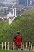A London man holds a tennis ball, awaiting his dog while looking down on the Cutty Sark from Greenwich Park.