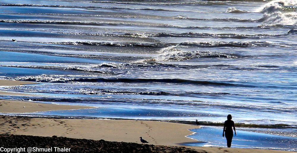 A visitor to Seabright State Beach in Santa Cruz, California walks along the tidal zone on November 16 as the ebb and flow of the tide creates a striking pattern on the shore.