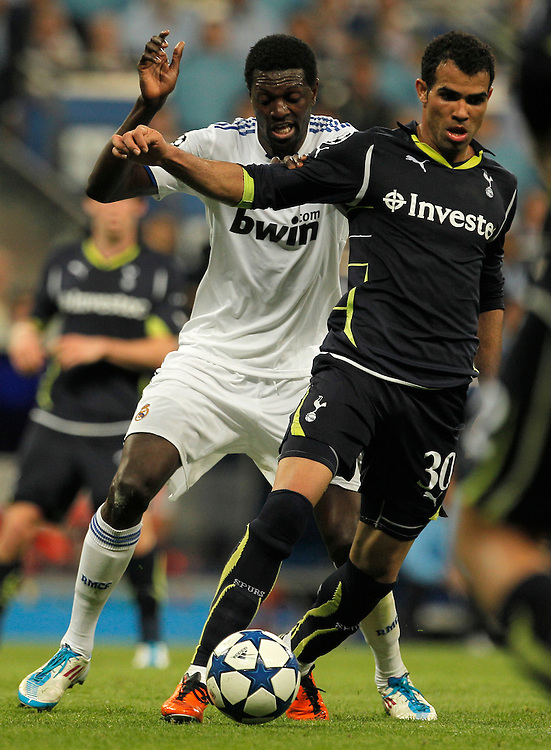 Real Madrid's Emmanuel Adebayor from Togo, left, vies for the ball with Tottenham Hotspur's Sandro from Brazil, left, during a quarter final, 1st leg Champions League soccer match at the Santiago Bernabeu stadium in Madrid, Tuesday, April 5, 2011.