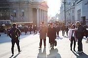 2 men walking through Trafalgar sq. London. 17 March