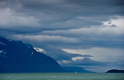 A sailboat sailing in brisk winds in the Lynn Canal near Haines, Alaska. The 90 mile, 2,000 foot deep Lynn Canal is known for its beauty -- magnificent mountains and glaciers. It is the deepest fjord in North American and one of the longest and deepest in the world.