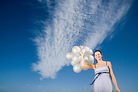 Woman holding balloons against sky portrait low angle view