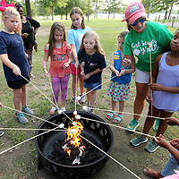 Myra Collins, Chief Girl Experince Officer with the Girl Scouts Heart of the South, helps area girl scouts roast marshmallows at Ballard Park Friday night as they gather to celebrate National S'Mores Day.