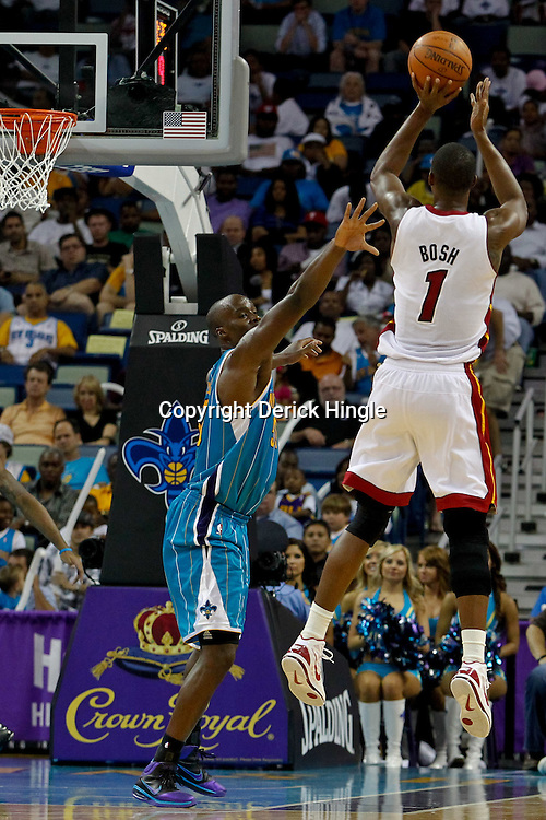 October 13, 2010; New Orleans, LA, USA; Miami Heat power forward Chris Bosh (1) shoots over New Orleans Hornets center Emeka Okafor (50) during the second half of a preseason game at the New Orleans Arena. The Hornets defeated the Heat 90-76. Mandatory Credit: Derick E. Hingle