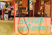 12 MARCH 2013 - ALONG HIGHWAY 13, LAOS:  A gas station with manual pumps on the side of Highway 13 in rural Laos. The paving of Highway 13 from Vientiane to near the Chinese border has changed the way of life in rural Laos. Villagers near Luang Prabang used to have to take unreliable boats that took three hours round trip to get from the homes to the tourist center of Luang Prabang, now they take a 40 minute round trip bus ride. North of Luang Prabang, paving the highway has been an opportunity for China to use Laos as a transshipping point. Chinese merchandise now goes through Laos to Thailand where it's put on Thai trains and taken to the deep water port east of Bangkok. The Chinese have also expanded their economic empire into Laos. Chinese hotels and businesses are common in northern Laos and in some cities, like Oudomxay, are now up to 40% percent. As the roads are paved, more people move away from their traditional homes in the mountains of Laos and crowd the side of the road living off tourists' and truck drivers.    PHOTO BY JACK KURTZ