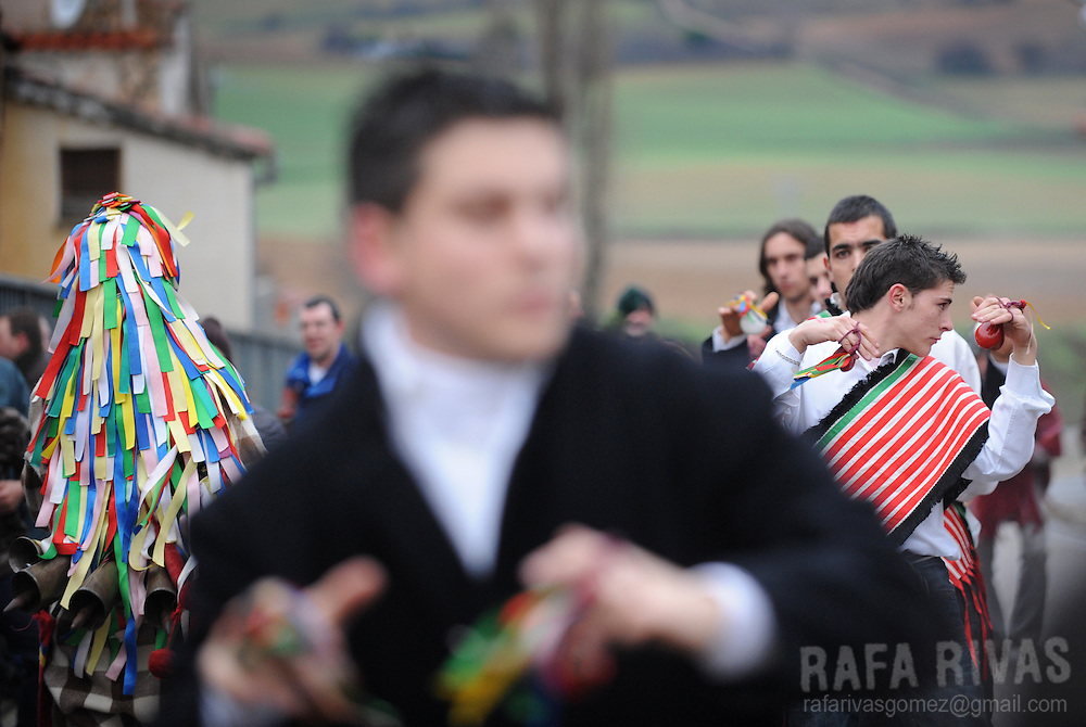 A man dressed in a Zangarron custom (L) chases people to whip them while the young men of the village dance, during the San Esteban festivity in Sanzoles del Vino, Zamora province, on December 26, 2009. The pagan festival of Zangarron opens the winter mascarades' season in Zamora province, and it is celebrated to help the young men to become adults. Zangarron gives chase to children and the elderly people of the town as his mission is to protect the local eighteen years old boys from the people, so they can dance. Zangarron wears a black leather mask, colourful clothes and a stick with pig's bladders. Bladders represent fertility and the cowbells tied to his back frighten away the evil spirits.