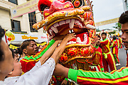 24 SEPTEMBER 2014 - BANGKOK, THAILAND: People make donations to Chinese Dragon dancers performing on Yaowarat Road in Bangkok's Chinatown during the Vegetarian Festival Parade. The Vegetarian Festival is celebrated throughout Thailand. It is the Thai version of the The Nine Emperor Gods Festival, a nine-day Taoist celebration beginning on the eve of 9th lunar month of the Chinese calendar. During a period of nine days, those who are participating in the festival dress all in white and abstain from eating meat, poultry, seafood, and dairy products. Vendors and proprietors of restaurants indicate that vegetarian food is for sale by putting a yellow flag out with Thai characters for meatless written on it in red.    PHOTO BY JACK KURTZ
