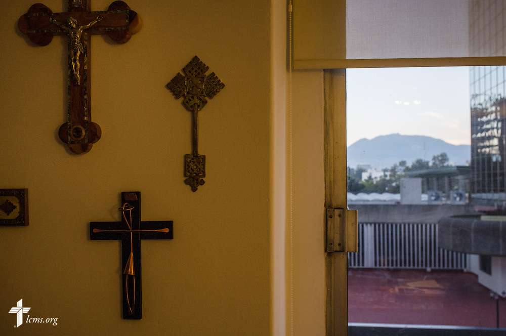 Crosses hang on the wall as the sun rises over Mexico City, seen from an apartment on Sunday, Jan. 15, 2017.  LCMS Communications/Erik M. Lunsford