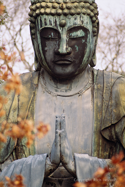 Close-up view of bronze Buddha statue at Gokokusan Tennoji (temple) in the Yanaka district of Tokyo, Japan