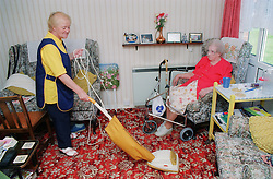 Elderly carer assisting client by hoovering front room,