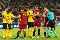 referee Milorad Mazic in discussion with Stefan Savic of Club Atletico de Madrid and Edin Dzeko of AS Roma during the UEFA Champions League group C match match between AS Roma and Atletico Madrid on September 12, 2017 at the Stadio Olimpico in Rome, Italy.