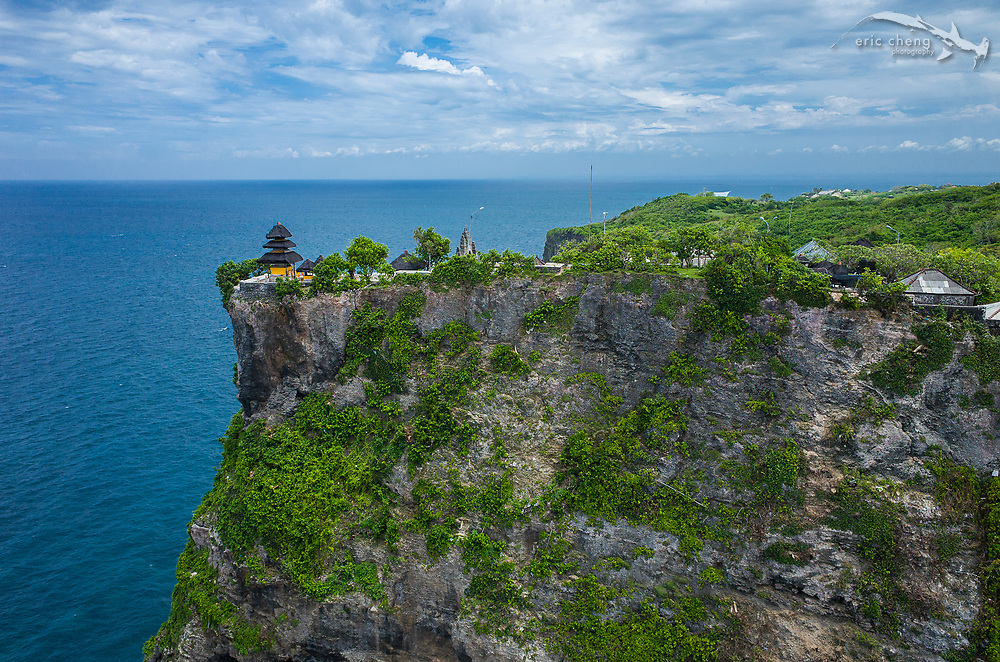 A rare, aerial perspective of Pura Luhur Uluwatu, a Balinese sea temple in Bali, Indonesia. The temple sits on a sheer cliff, and guards Bali from evil spirits from the south-west.