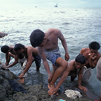 Philippines, Negros Island, Workers wash up in sea after unloading cement from cargo ships at Bacolod's cargo port.