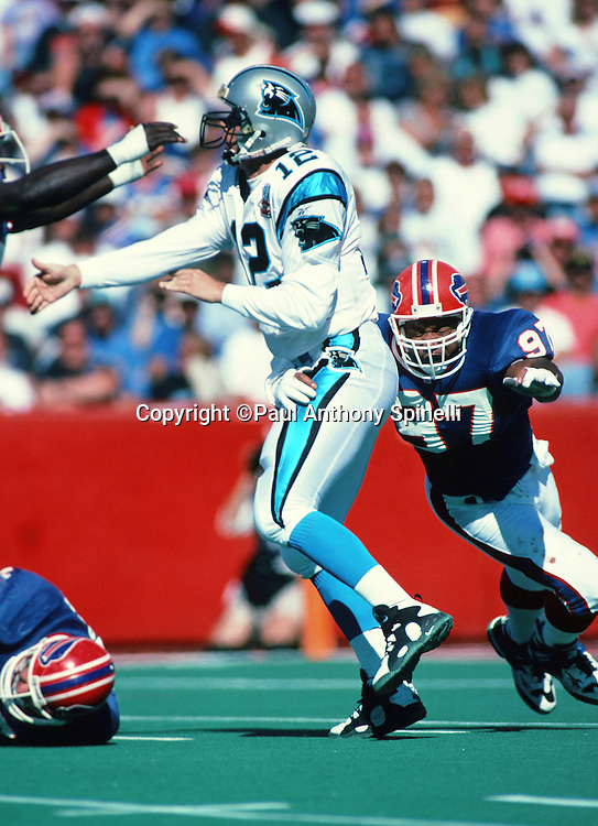 Carolina Panthers quarterback Kerry Collins (12) gets hit by Buffalo Bills linebacker Cornelius Bennett (97) and pressured from the front by Buffalo Bills  defensive end Bruce Smith (78) while throwing a pass during the NFL football game against the Buffalo Bills on Sept. 10, 1995 in Orchard Park, N.Y. The Bills won the game 31-9. (©Paul Anthony Spinelli)