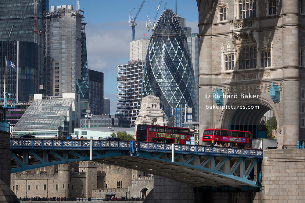 Two London buses cross a cityscape of the City of London in the background with the northern abutment tower of Tower Bridge, on 5th October, 2017, in London, England.