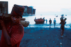 BANGLADESH CHITTAGONG MADHOM BIBIR HAT OCT00 - Labourers carry onto land any loose fittings from a recently beached ship. Doors, furniture and bathroom fittings fetch good prices on local markets and add to the income of the ship-breaking entrepreneurs who are primarily concerned with recycling the scrap metal...Several thousand labourers work on one medium-sized (50,000 ton) ship for a period of around three months, until it is completely dismantled and taken apart. ..Since Bangladesh does not possess mineral resources such as iron ore, it works out more cost-efficient to employ a large army of day-labourers to recycle the scrapped ships rather than to import ore. On average, a labourer can expect to earn a little more than 1 US Dollar per day...jre/Photo by Jiri Rezac..© Jiri Rezac 2000..Contact: +44 (0) 7050 110 417.Mobile: +44 (0) 7801 337 683.Office: +44 (0) 20 8968 9635..Email: jiri@jirirezac.com.Web: www.jirirezac.com..© All images Jiri Rezac 2000 - All rights reserved.