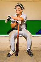 Baseball Player in Dugout With Bat