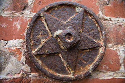 A rusted star shaped iron fixture on a brick wall exterior of a building in Fisherman's Wharf, San Francisco, California