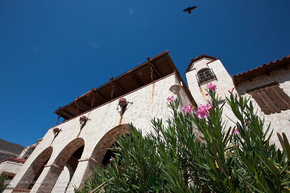 A crow flies above Scotty's Castle - Death Valley National Park, California