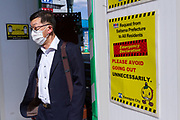 A Japanese salaryman, wearing a surgical mask walks past signs urging people to stay home and keep social distancing at Kawagoe station in Saitama, Japan. Thursday May 7th 2020 The month-long state of emergency declared by the Japanese government in response to the COVID-19 pandemic was due to end on May 7th but was extended to May 31st despite Japan appearing to have avoided the high infection and mortality rates of some countries. Areas like Shibuya have many businesses shuttered and closed and the streets are a lot quieter than usual.