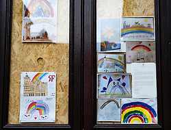 Childrens' drawings of rainbows in window of Balmoral Hotel which is closed and boarded up during the coronavirus pandemic lockdown in Edinburgh, Scotland, UK