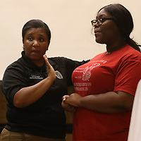 Lt. Katarsha White demonstrates a self defense move on attendee Uriah Coleman, 17, during the G.I.R.L. Talk event