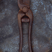 Pair of rusty old secateurs lying on tarnished metal plate