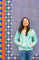 An early 30's late 20's Asian (japanese / filipino) woman smiling in front of a colorful mosaic background..Model Release: 20070513_MR_A