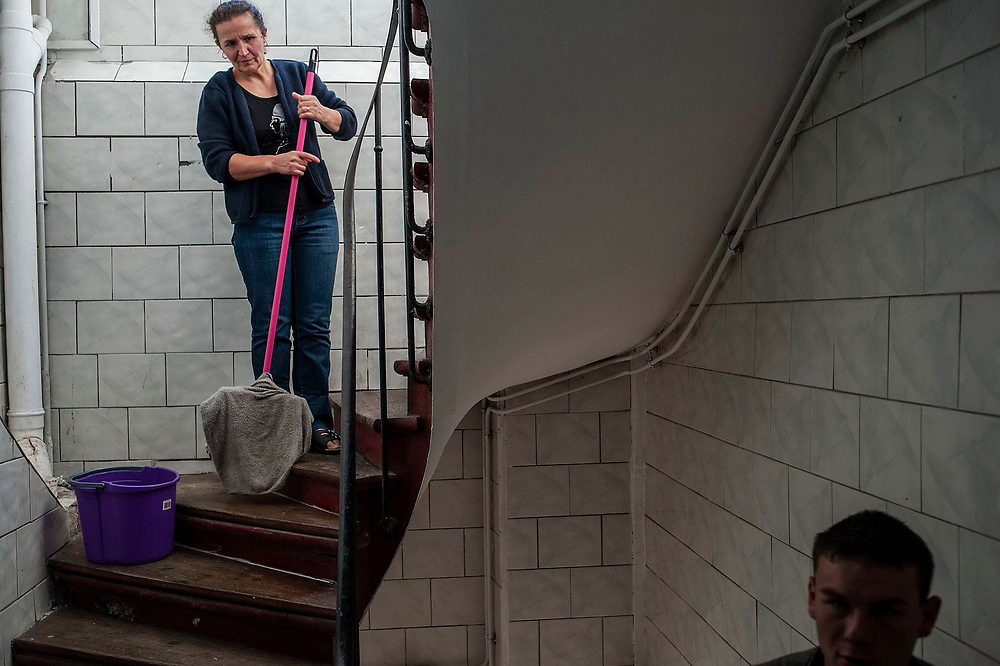Lica Sas from Certeze village in Romania cleans the stairs of the building where she lives in Saint Denis near Paris.