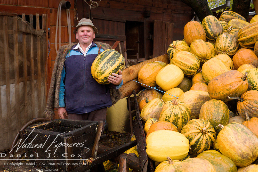A Romanian man proudly displays his fall harvest of assorted squash.