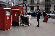 Man uses his smartphone with his red suitcase near red postal boxes in the heart of City of London's financial district.