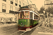 Digitally enhanced image of a Green tram in the crowded narrow streets of Lisbon, Portugal