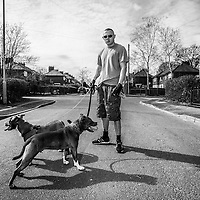 A man poses for a photo with his two dogs on a Wythenshawe housing estate, Manchester, England.