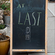 Blackboard humorous  outdoor restaurant sign. <br /> <br /> &quot;At Last&quot; (symbol of clock at midnight for New Years )