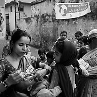 """Administering the polio vaccination outside the Madrassa Abdul Salam in Pakbara town, Taspur Block, Moradabad. The clinic was inaugurated by Shamme Alam Shahar Imam (not photographed). <br /> <br /> In September 2006, Pakbara town in Taspur Block achieved 86 percent polio vaccination coverage. For the November 12th BMCs (Block Mobilisation Coordinators) and CMCs (Community Mobilisation Coordinators) were aiming for above 90percent. With poor sanitation and overcrowded living conditions, Pakbara town is considered a high risk polio infection area. The population of Pakbara town is 40-50,000. In Taspur block there are four BMCs. Together they have informally labeled the November 12th round """"Mission New Born"""". The next round will be """"Mission X-R"""" with a focus on families refusing to have their children vaccinated. <br /> <br /> Photo: Tom Pietrasik<br /> Moradabad, Uttar Pradesh, India.<br /> November 12th 2006"""