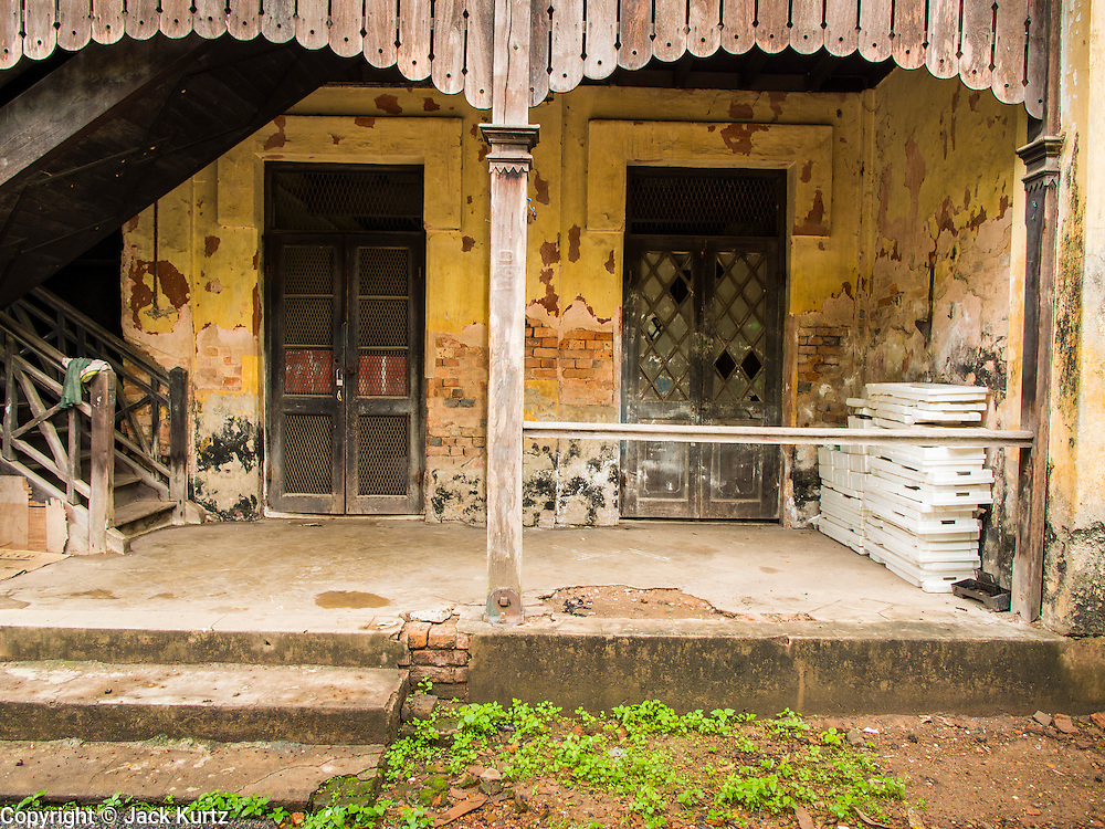 07 JUNE 2014 - YANGON, MYANMAR: The entrance to a teak building in the Pegu Club. The Pegu Club in Yangon was the Officers' Club for the British Army when Myanmar was the British colony of Burma. The club, principally made of teak, is now abandoned and in decay. Squaters have moved into the parts of the complex still standing. Yangon has the highest concentration of colonial style buildings still standing in Asia. Efforts are being made to preserve the buildings but many are in poor condition and not salvageable.    PHOTO BY JACK KURTZ