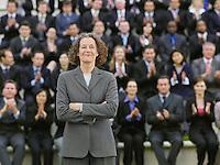 Business woman standing in front of business people sitting in bleachers clapping portrait